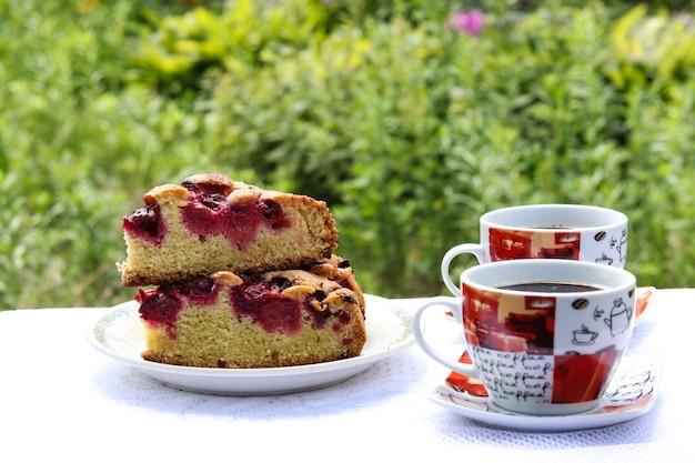 Stukken van een taart met een kers en twee kopjes koffie op een tafel buiten. horizontaal formaat