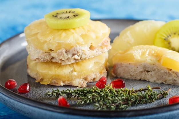 Stukken van gebakken varkensvlees met ananaskaas en kiwi op grijze plaat en blauwe achtergrond