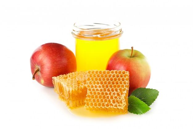 Stukken van honingraat, appels en glazen pot geïsoleerd op wit