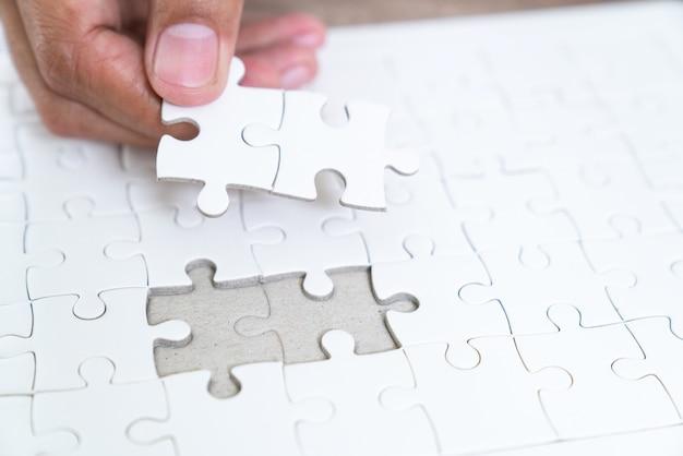 Stukken van legpuzzel op palm, stukken van puzzel in de handen van de mens