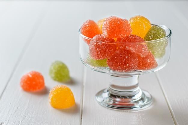 Stukken van mooie marmelade in een glazen kom op een witte tafel. heerlijke snoepjes gemaakt van gelei met suiker.