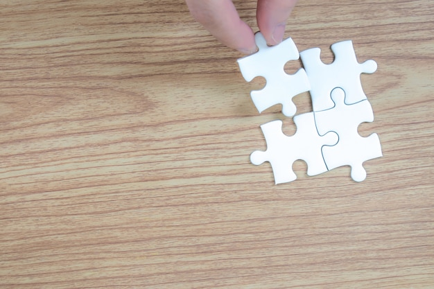 Stukken van puzzelstukjes in menselijke handen.