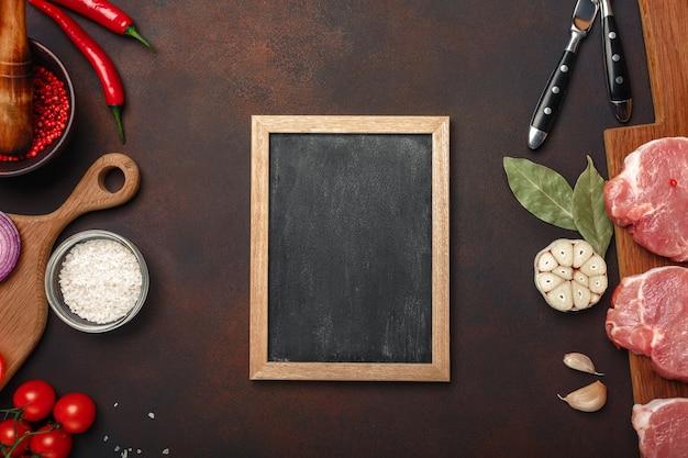 Stukken van rauw varkensvlees biefstuk op snijplank met cherrytomaatjes, rozemarijn, knoflook, rode paprika, laurier, ui, mortel en krijt bord op roestige bruine achtergrond