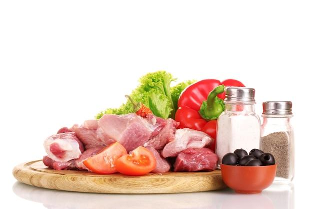 Stukken van rauw vlees en groenten op een houten bord op wit wordt geïsoleerd