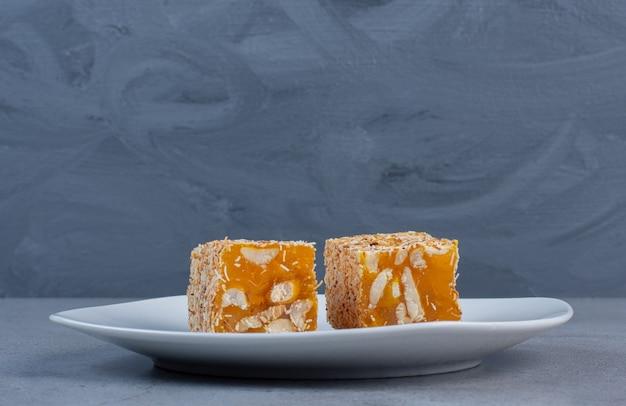 Stukken van turkse lekkernijen bedekt met gestrooid snoep op een witte schotel op marmeren achtergrond.