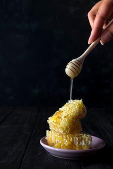 Stukken van verse honingraat met een houten dipper druipende honing op een keramische plaat