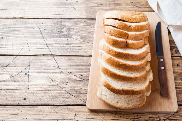 Stukken van wit broodbrood voor toost op een houten lijst.
