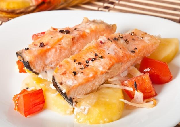 Stukken zalm met aardappelen, tomaten en uien gebakken in de oven