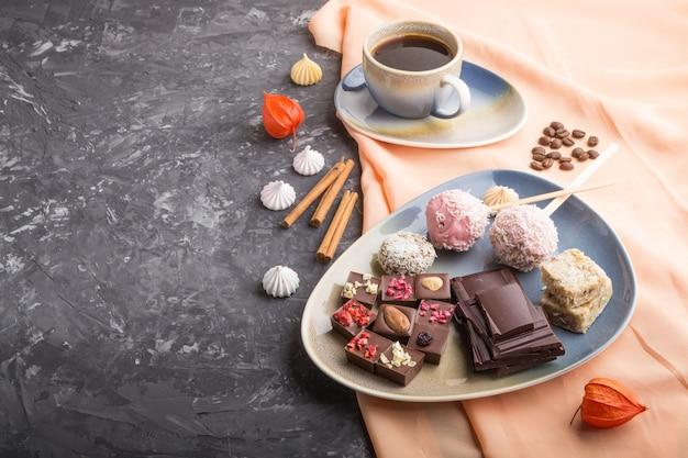 Stukken zelfgemaakte chocolade met kokossuikergoed en een kop koffie. zijaanzicht
