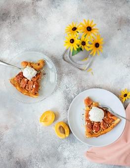 Stukken zelfgemaakte taart met abrikozen en ijs