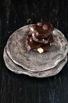 Stukken zwarte chocolade liggen op een donker bord dat op een zwart oppervlak staat
