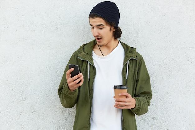 Stupefied tiener speelt online games op smartphone, draagt afhaalkoffie, heeft verbaasd gekeken naar het scherm van mobiel