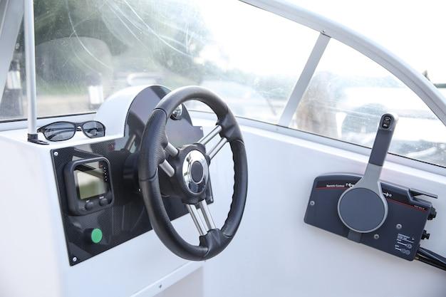Stuurwiel en kuip van de witte motorboot