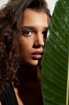 Stylidh vrouw verbergend gezicht achter groot groen blad