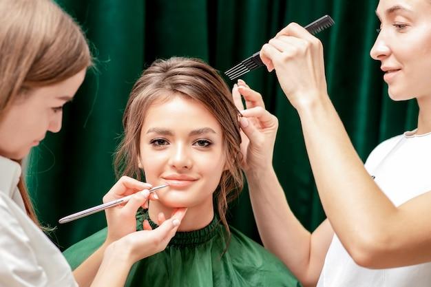 Styling haar en het toepassen van lippenstift lip voor jonge vrouw close-up.