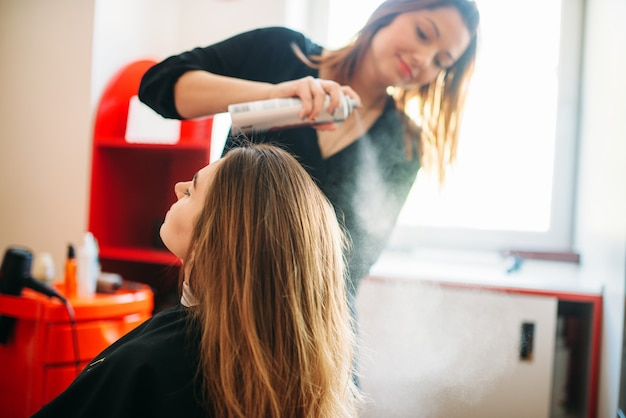 Stylist bereidt zich voor om mousse, vrouwelijke haarsnit toe te passen in de kapsalon. kapsel maken in schoonheidssalon