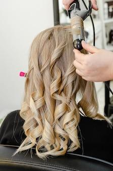Stylist die een kapsel met haarkrulspeld maakt voor blonde vrouw na haarverven. schoonheidssalon concept.