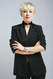 Stylist in elegant zwart pak camera kijken, expert in mode. persoon op het gebied van mode, trendy blonde vrouw met veel accessoires. winkelen, binnenshuis, close-up