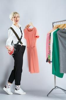 Stylist in modieuze outfit jurken op rek, volledige lichaam te onderzoeken. persoon op het gebied van mode kleding kiezen, camera kijken en breed glimlachen. winkelen, binnenshuis