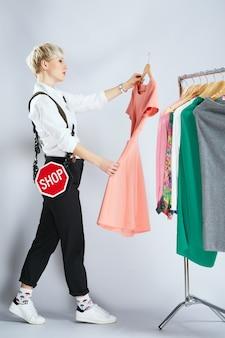 Stylist in modieuze outfit jurken op rek, volledige lichaam te onderzoeken. persoon op het gebied van mode kleding kiezen. winkelen, binnenshuis, profiel