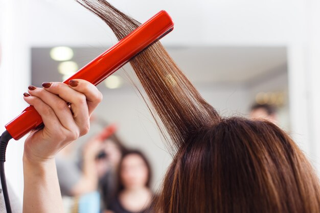 Stylist lijnt het haar van de klant uit met een stijltang