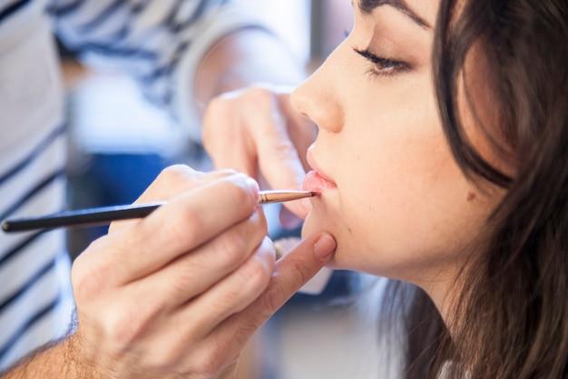 Stylist lip make-up zetten op een mooie vrouw