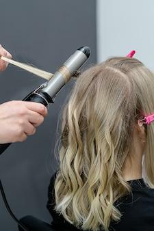 Stylist maakt een kapsel met haarkrulspeld voor blonde vrouw na het verven van het haar. kapsalon concept.