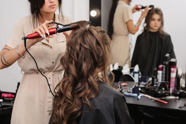 Stylist maakt krullen curling meisje met lang bruin haar in een professionele schoonheidssalon