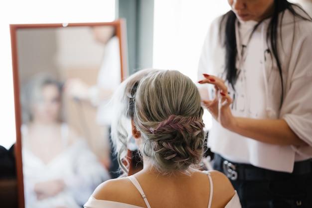Stylist maakt van de bruid voor de spiegel een mooi kapsel