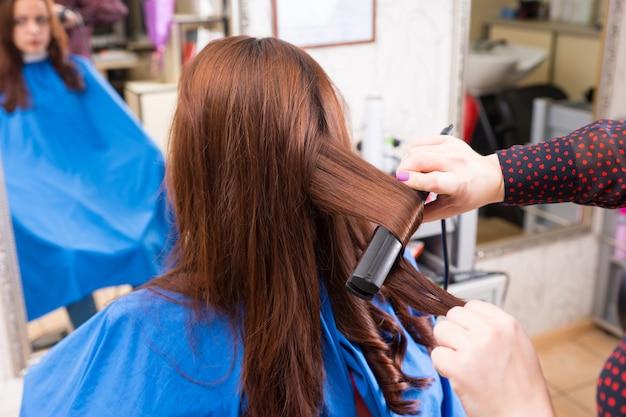 Stylist met behulp van stijltang op haar van brunette client
