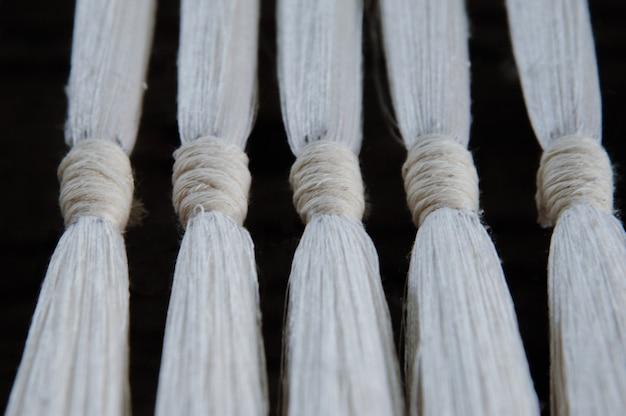 Subtiele zijde wevende draad en garen close-up. witte katoenvezel