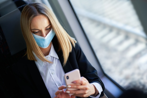 Subway forens zakenvrouw in masker op openbaar vervoer met smartphone