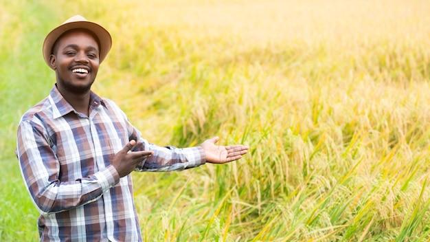 Succes afrikaanse boer glimlachend op een biologische rijstboerderij. landbouw- of teeltconcept