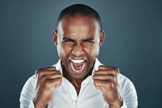 Succes behaald. knappe jonge afrikaanse man in shirt gebaren en schreeuwen terwijl hij tegen een grijze achtergrond staat