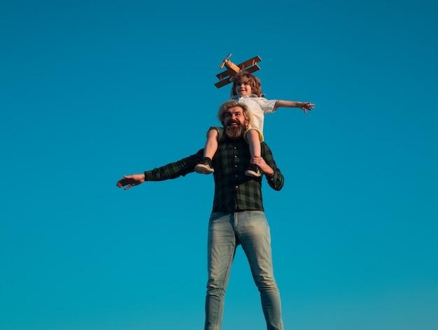 Succes en kind leider concept. vader en zoon spelen met speelgoedvliegtuig buiten. gezinsvakantie, ouderschap. vaderdag.