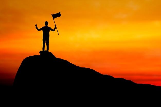 Succes en silhouet van de winnaarvlag van de zakenmanholding op berg, leider, voltooiing en winstconcept