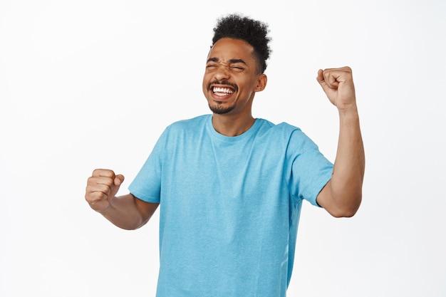 Succes. gelukkige afro-amerikaanse man, sportfan zingen, tevreden glimlachen, doel bereiken, wroeten voor team, blij met goede score, vuistpomp in triomf, staande op wit.