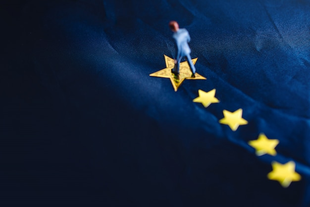 Succes in zaken of talentconcept. bovenaanzicht van een miniatuur zakenman permanent op een gele gouden ster