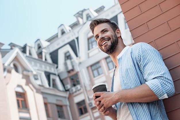Succes is gemoedsrust portret van zelfverzekerde bruinharige man die een koffiekopje vasthoudt en glimlacht