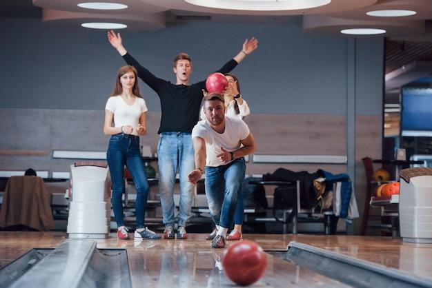 Succes. jonge vrolijke vrienden vermaken zich in het weekend in de bowlingclub