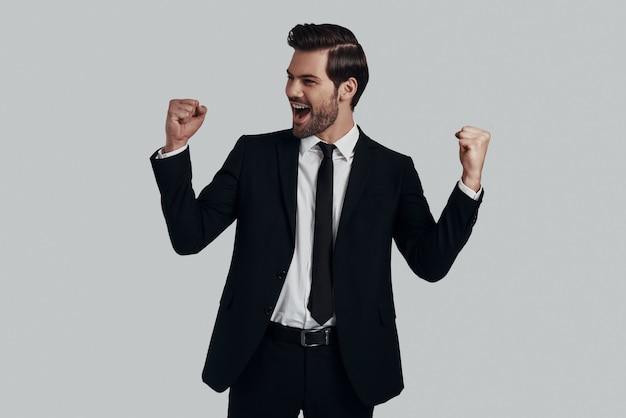 Succes! knappe jonge man in volledig pak gebaren en schreeuwen terwijl hij tegen een grijze achtergrond staat