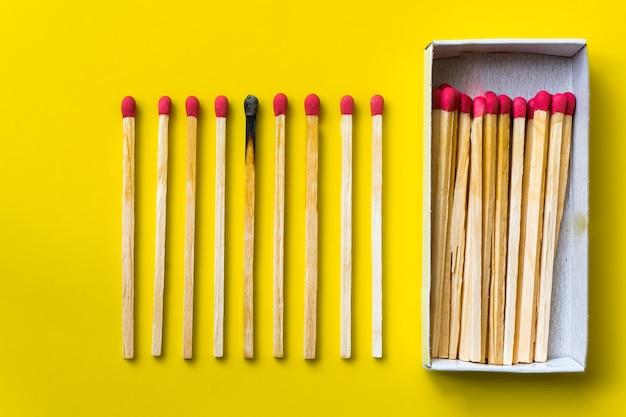 Succes, nederlaag, prestatie. het concept van geluk. komt overeen met een gele achtergrond. verbrande donkere wedstrijd tussen normale wedstrijden. brandend lucifervuur voor zijn buren, een metafoor voor ideeën en inspiratie