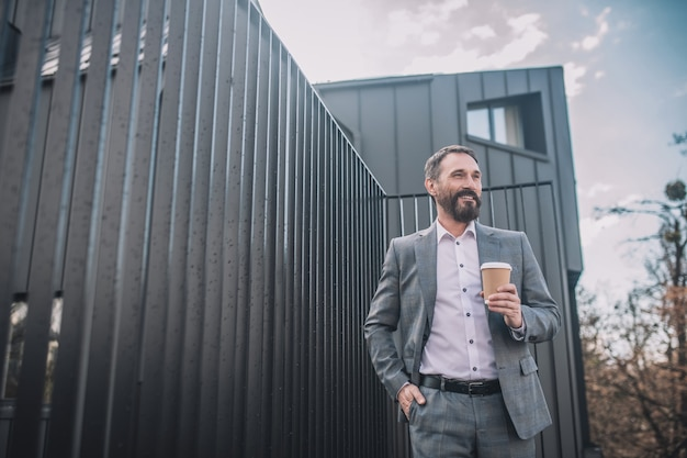 Succes. succesvolle lachende zakenman in grijs pak met koffie in de buurt van kantoor op straat in een goed humeur