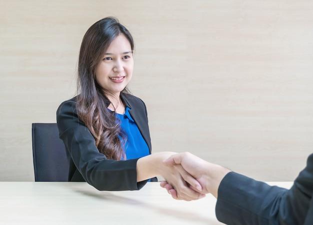Succes van de close-up het aziatische vrouw om zaken met iemand met gelukkig gezicht te behandelen