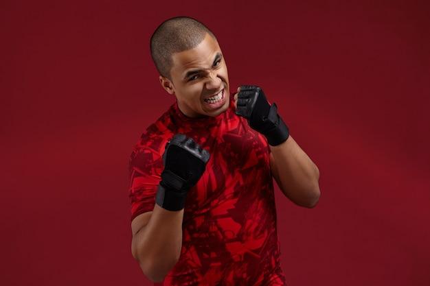 Succes, vastberadenheid, uitdaging en concurrentieconcept. foto van woedende agressieve jonge afro-amerikaanse vechter die zwarte trainingshandschoenen draagt die in studio boksen, brullen, zich voorbereiden op strijd