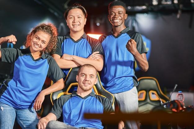 Succes vieren. gelukkig multiraciaal cybersportteam glimlachend in de camera en gebarend na esport-toernooi. competitie voor online videogames