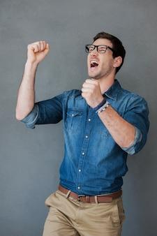 Succes vieren. opgewonden jonge man die zijn armen omhoog houdt en positiviteit uitdrukt