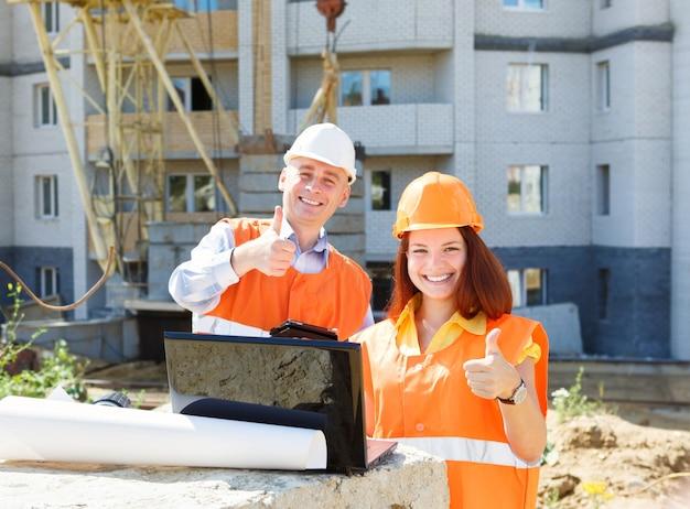 Succes vrouwelijke en mannelijke bouwvakkers met een laptop en tekeningen