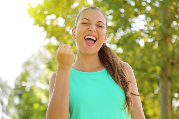 Succes winnaar fitness runner vrouw schreeuwt van tevredenheid met gesloten ogen en vuist omhoog energetische krachtige woede kracht bepaling kracht expressie vieren.