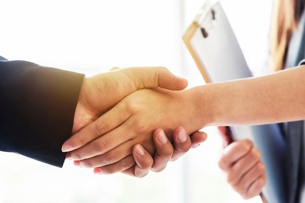Succes zakelijke deal concept. close-up van bedrijfsmensenhandenschudden na gebeëindigde overeenkomst in bureau.